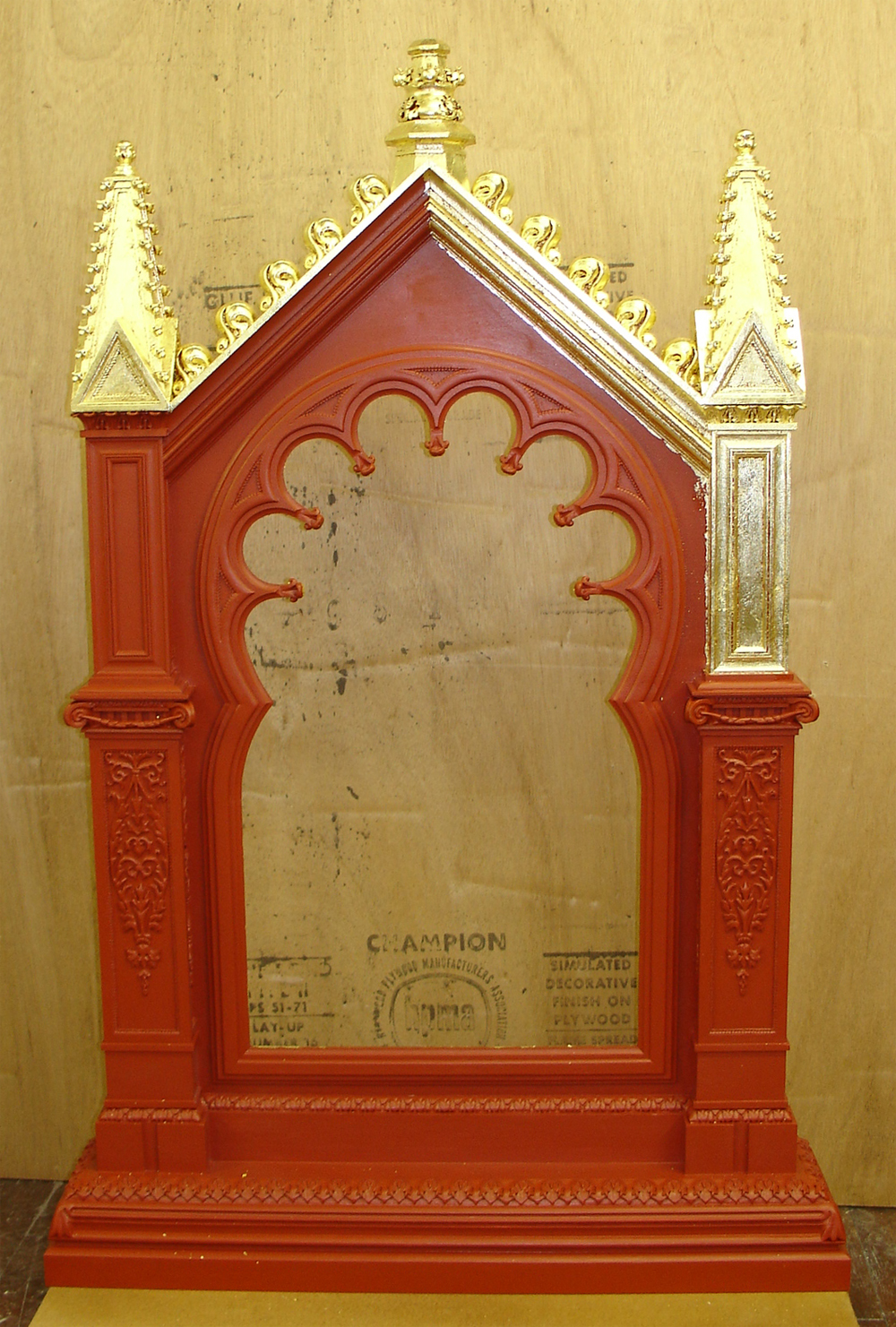 The frame with all of the ornament on, as well as the red bole, starting to be gold leaf gilded.