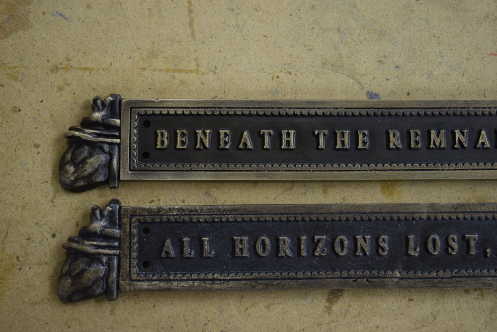 Comparison of the new title plate (top) and the original.
