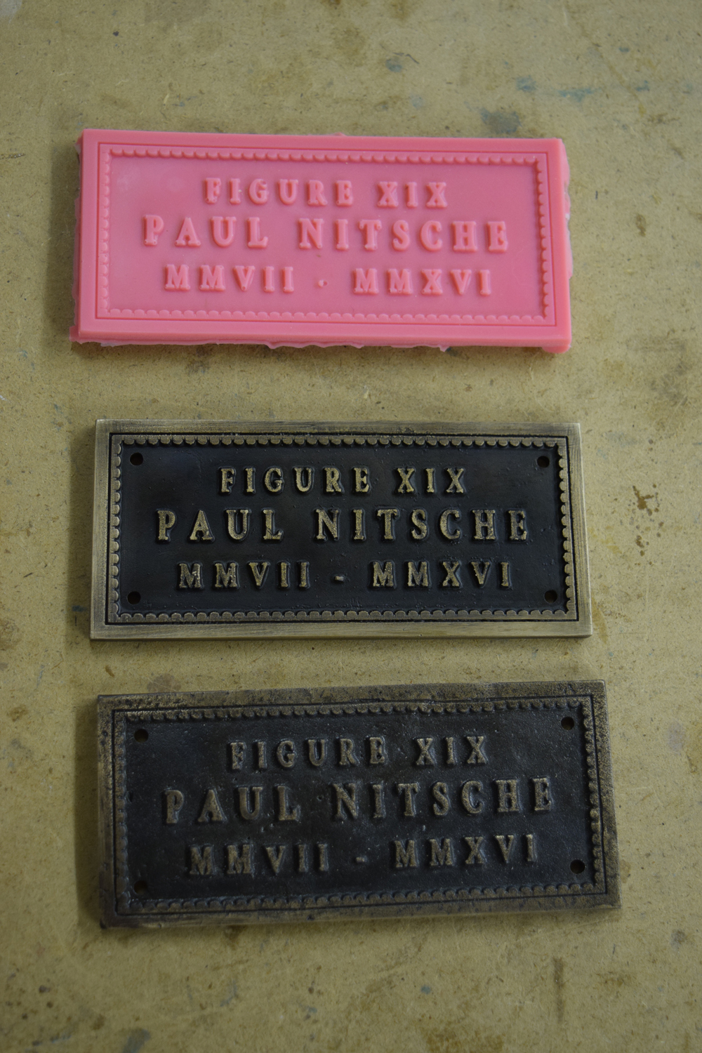Comparison of the title plates. The original wax (top), the new title plate (middle), and the original title plate (bottom).