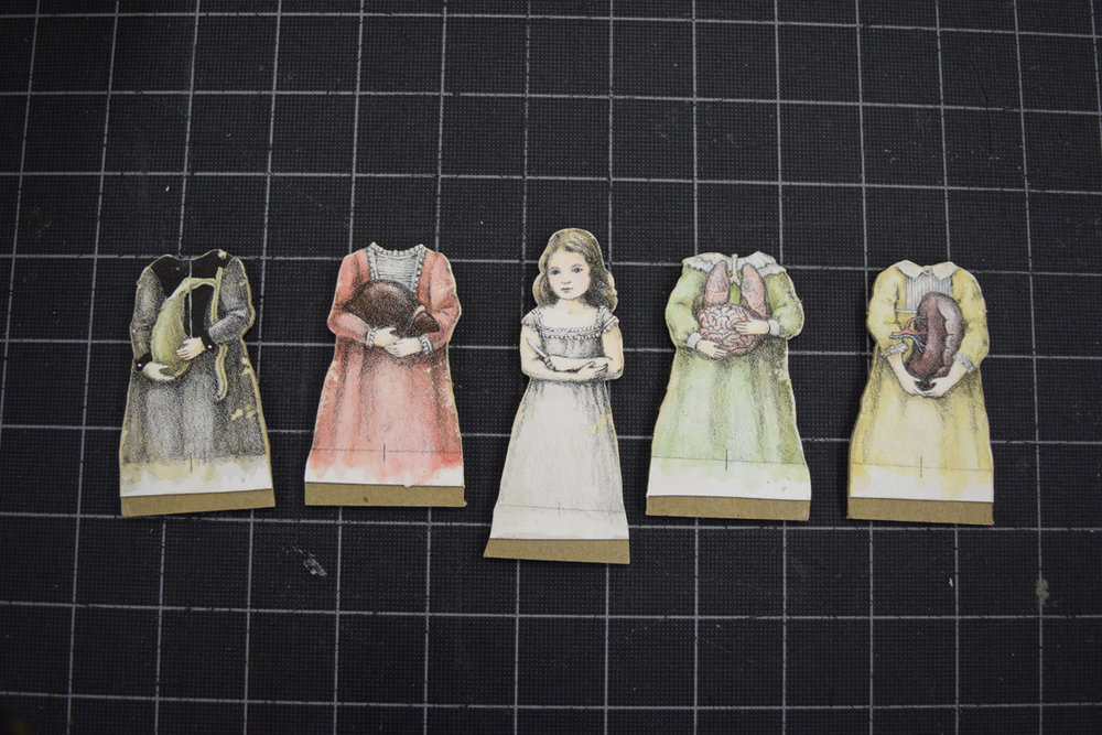 The finished dolls: Mounted to bookbinding board, cut out, and the edges distressed.