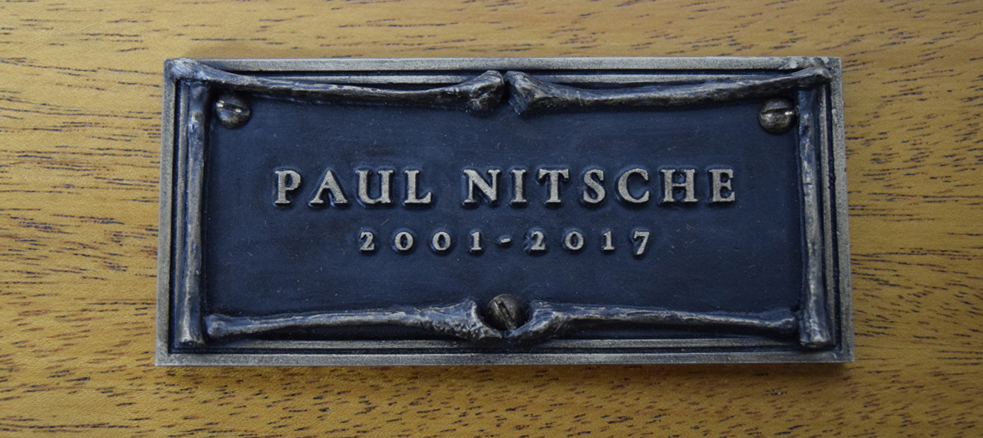 The finished bronze name plate with a liver of sulfur patina and clear coat.