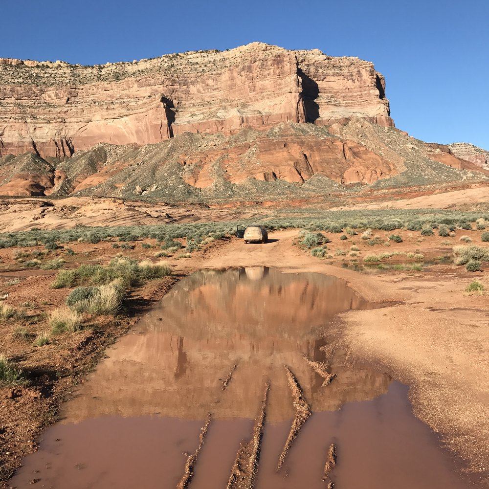 "Parked car at the ""trailhead."" Follow these cliffs to the south as you make your way to Reflection Canyon."