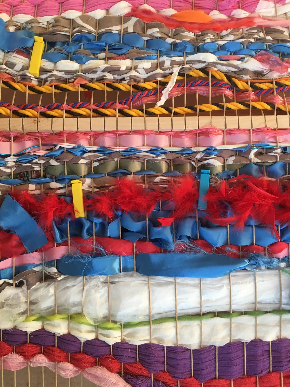 We wove rope, plastic, ribbon, scarves, sticks, feathers, and used clothing into the loom.