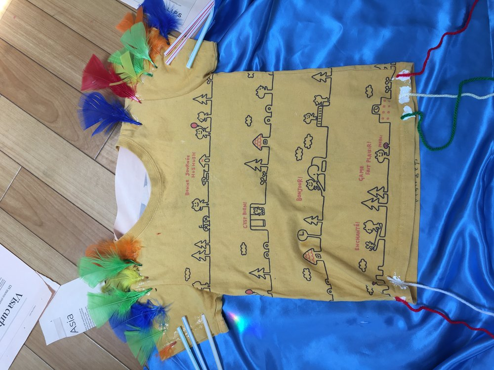 This old shirt was enhanced with feathers and straws using sticky tape. A cape was added to the back.