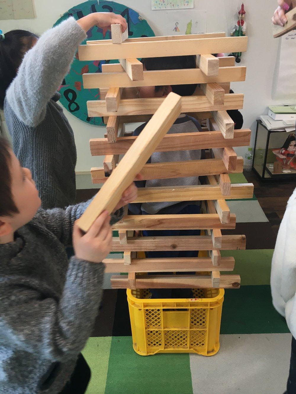 木製のブロックでタワーを作り始めた複数の児童たち