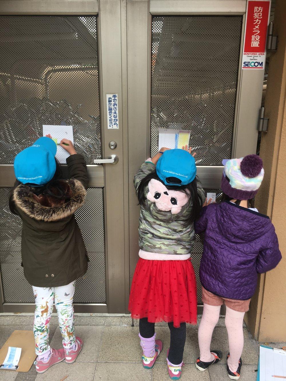 ゲートに紙をあててクレヨンでなぞり模様を写し取る児童