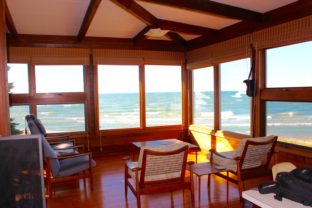 From this seating group on the porch the cottage floats over the sand and water of Lake Michigan