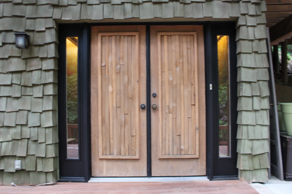 Glass lights flank the cedar covered double doors and create an inviting entry.