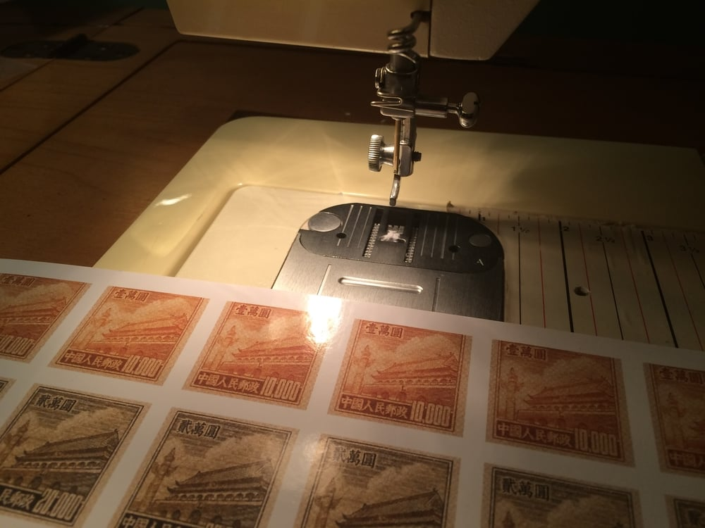 Perforating fake stamps with a hollow brass rod and a sewing machine.