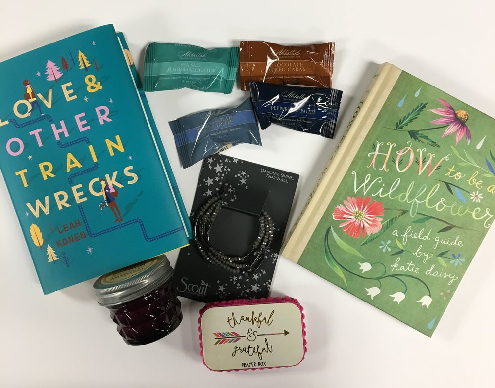 For girls: Love & Other Train Wrecks ($17.99); Chocolates ($.62); How to be a Wildflower ($19.95); Scout Bracelet ($28.00); Prayer Box ($12.99); Candle ($11.00)
