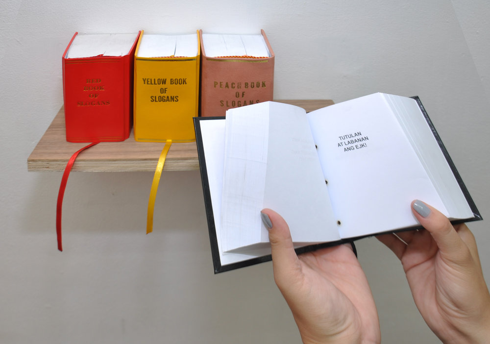 KIRI DALENA   Red Book of Slogans , 2008  Yellow Book of Slogans , 2010  Peach Book of Slogans , 2014  Black Book of Slogan , 2017 bound digital prints 10.25 x 13.25 x 6.6 cm   installation view
