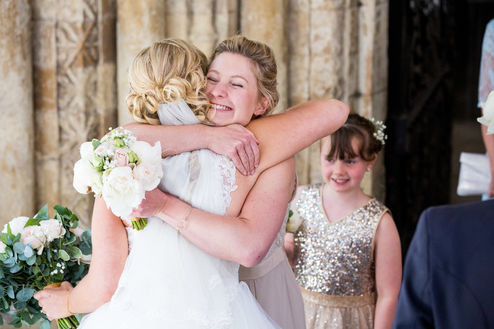 James Ireland Photography - Kent Wedding Photographer - A bridesmaid congratulates the bride after her wedding ceremony at The Inner Temple, London
