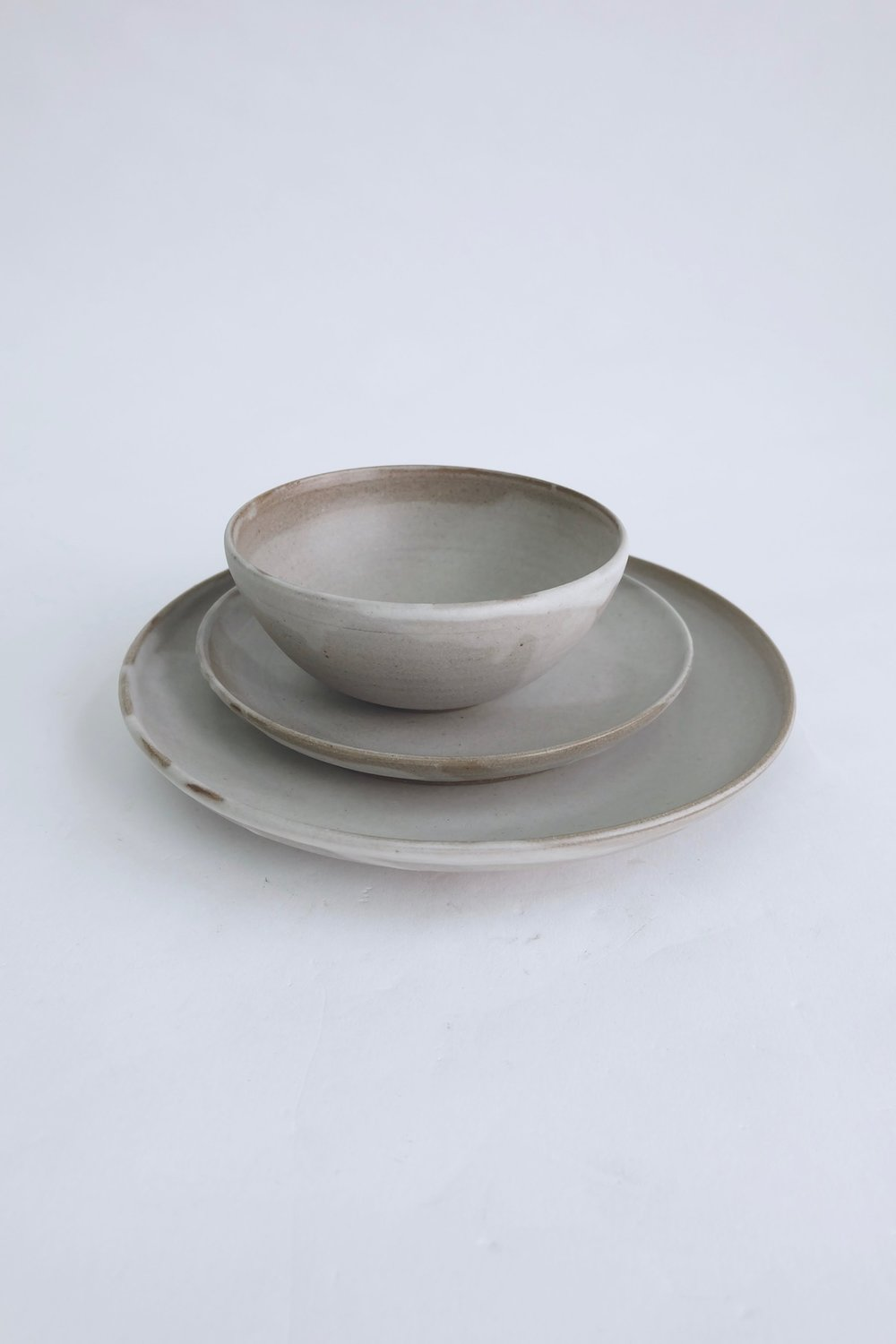 Dinnerware: 3-piece dinnerware for everyday use including a dinner plate, a salad/desert plate, and a soup/cereal bowl. I aimed to create the most versatile pieces that celebrate   the warmth and uniqueness of handmade objects.  Users can incorporate the pieces into their daily eating by themselves or with plates that users may already own. The neutral grey works well not only with colorful ingredients like beets and greens but also enhances white food items like rice and bread. It comes with a foot and can be used in both casual and dressed-up table setting.