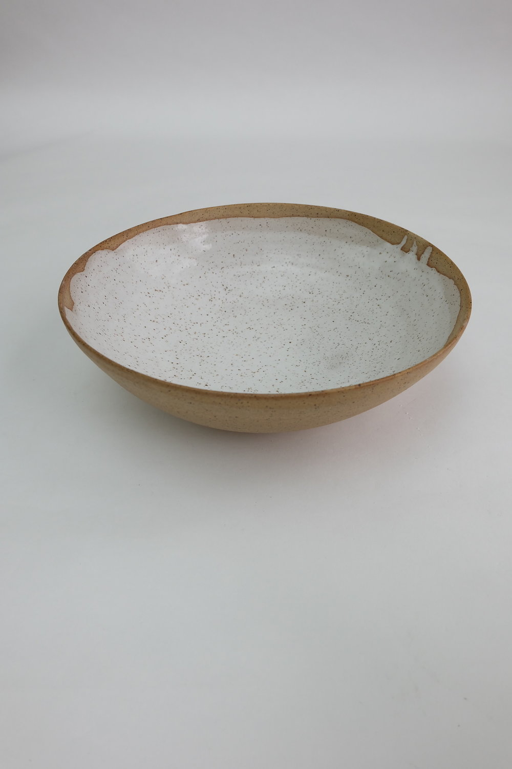 "13""diameter serving bowl finished in a milky glossy glaze contrasting with the rough texture of  natural clay."