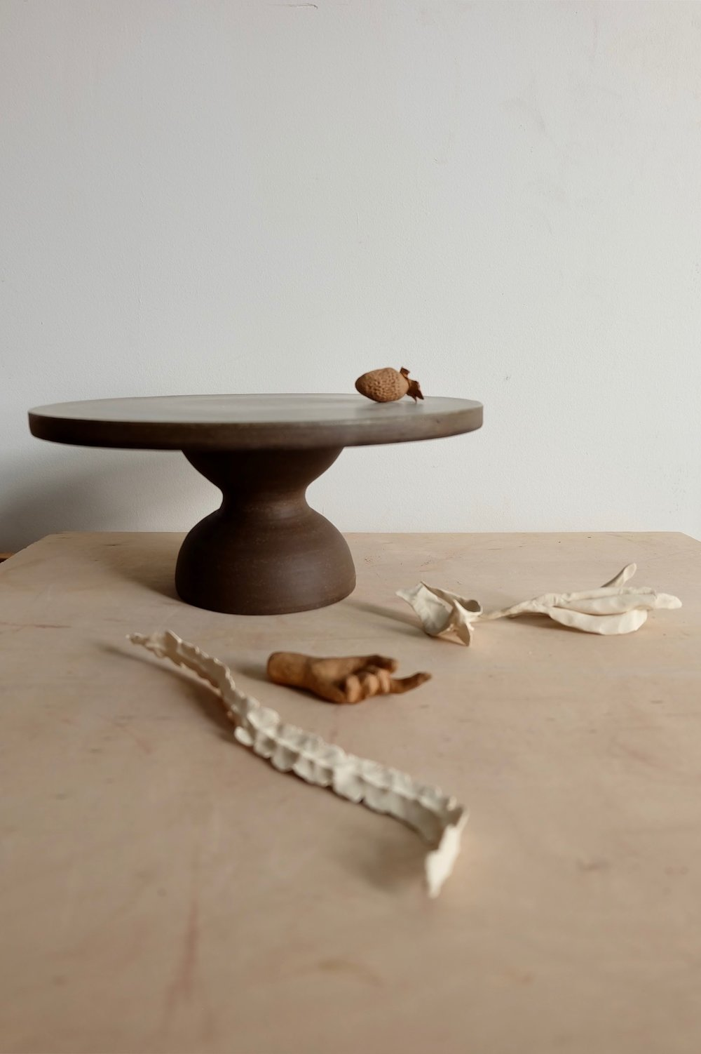 """A stand for 9"""" diameter cakes and pies in an earthy finish in a friendly form. It is a wheel thrown dark chocolate clay, finished in satin grey on the top surface."""