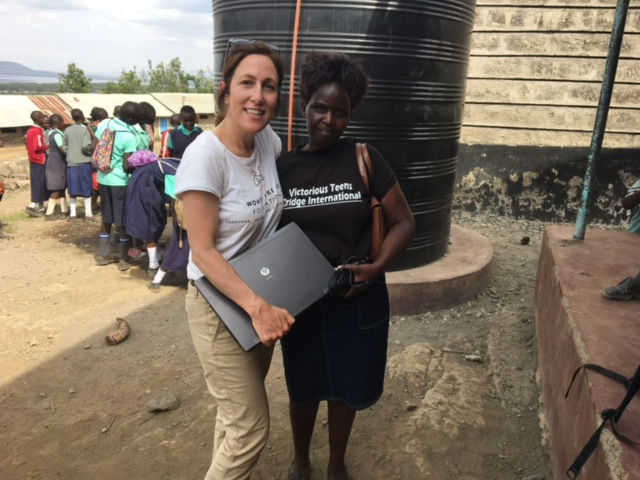 Angela Palmieiri giving Victorious Teens founder Ann Kabui a lap top for needed access to research and learning.
