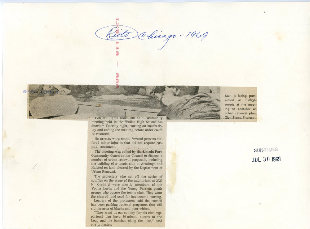 The back of a photo, including the clipped article and date it was published.
