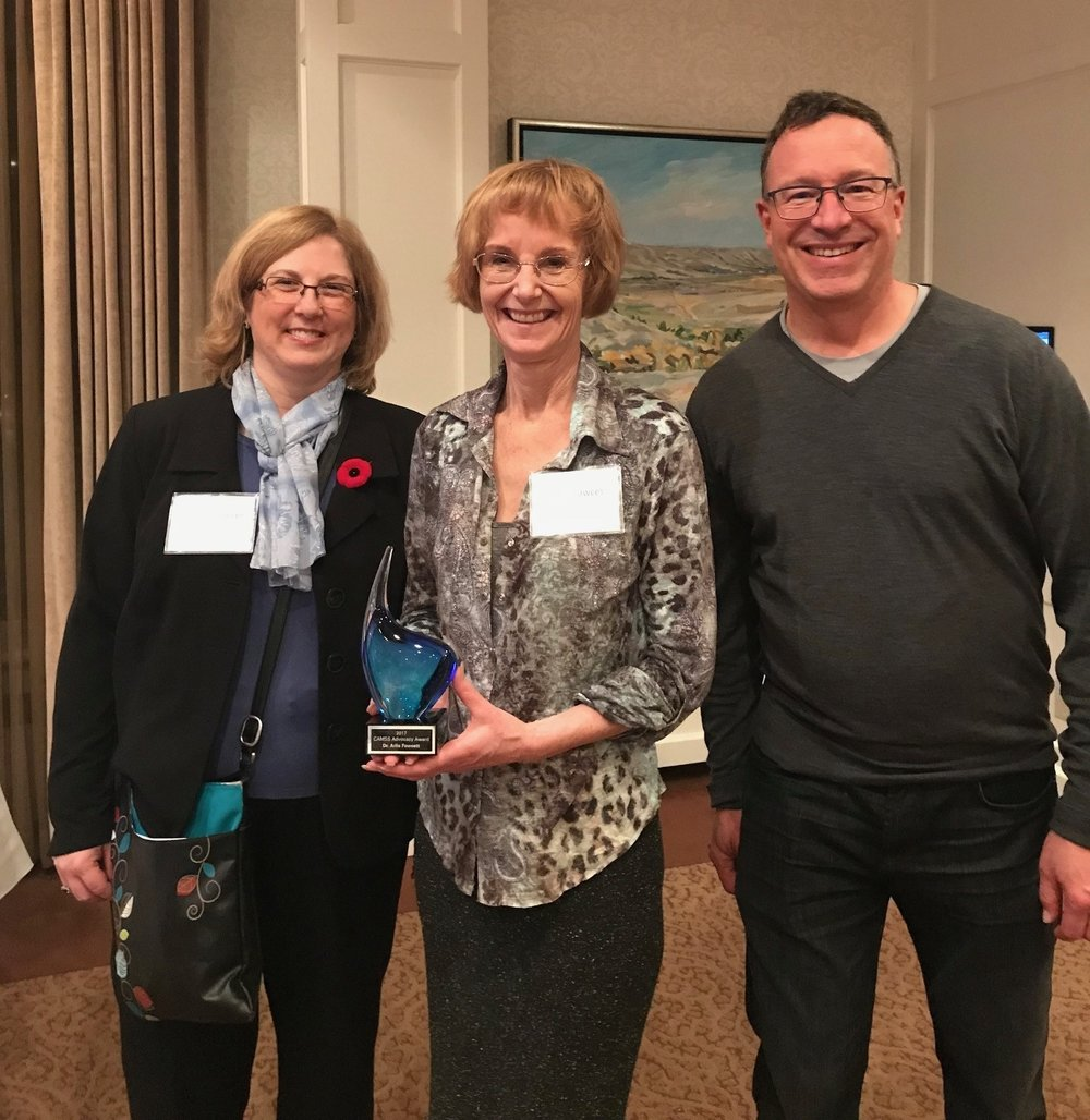 Dr. ARliE FAWCETT HOLDING THE ADVOCACY AWARD, ACCOMPANIED BY DR. SHARRON SPICER, WHO PRESENTED THE AWARD, AND DR. STEVE PATTERSON, WHO NOMINATED DR. FAWCETT