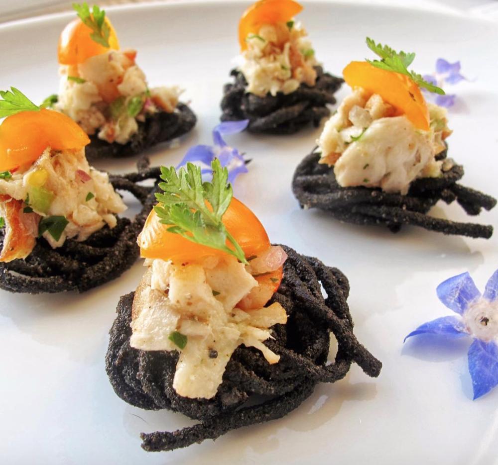 - Seafood salad on black pasta cake with marinated tomatoes