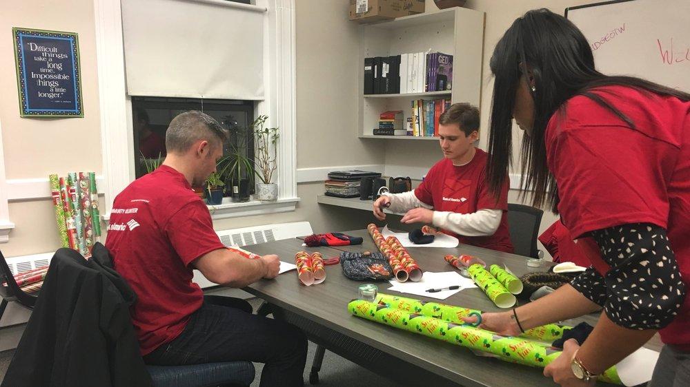 Bank of America volunteers help wrap gifts at Bridge Over Troubled Waters