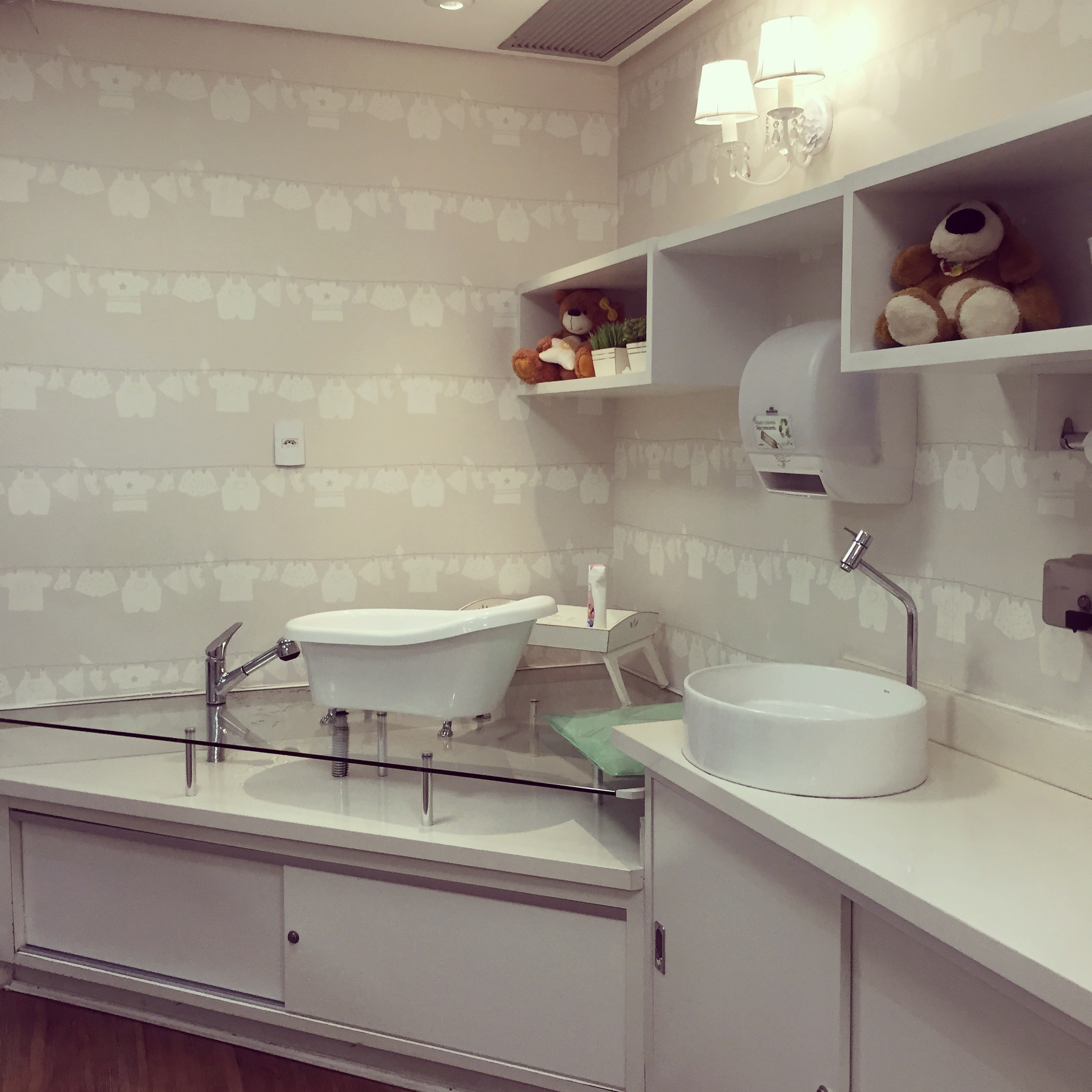 There is a bath, sink and any supplies you may need available. The wall is covered in a clothes line motif wallpaper in neutral colours, and there are shelves styled with stuffed toys and artificial  plants.