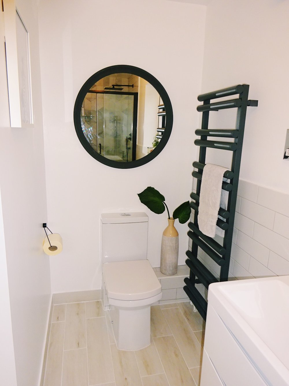 The white wood effect tiles for the floor are one of our favourite additions, I'd have them everywhere in the house! These are from  Walls and Floors . The tall black towel rail makes a statement and goes well with the round mirror which was an  IKEA  hack, I painted it to achieve that effect.