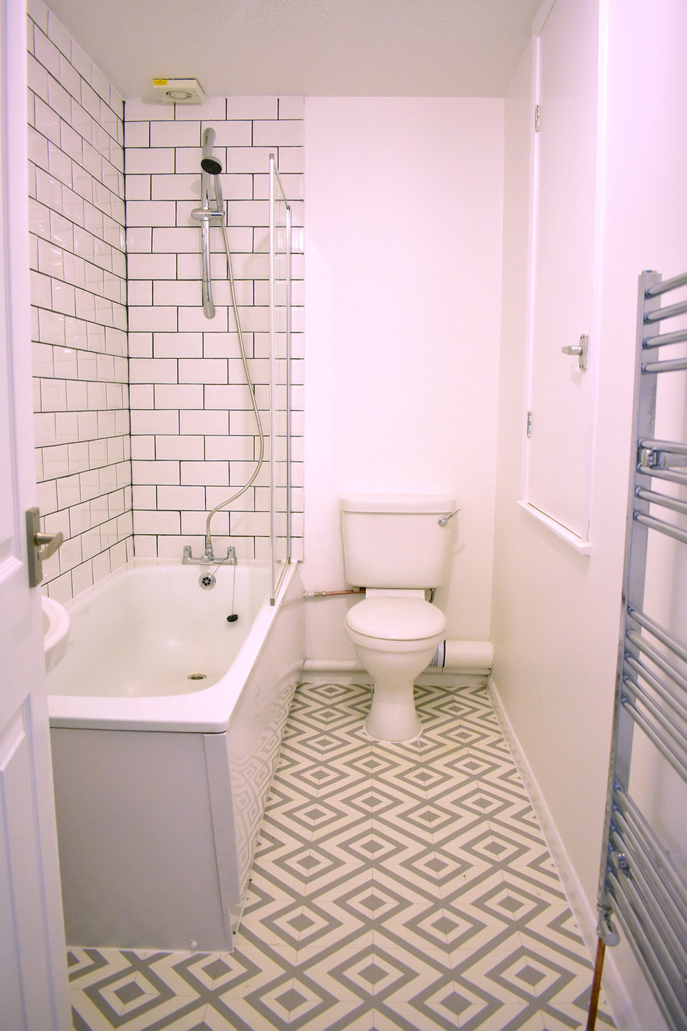 New tiles, vinyl flooring, and white paint made a world of difference in the bathroom