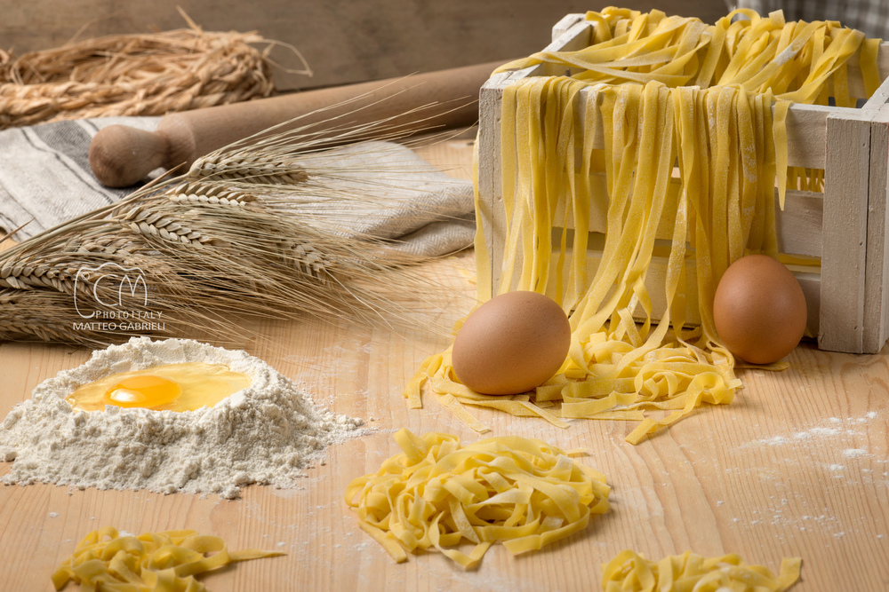 Tagliatelle, fresh homemade egg pasta and ingredients, Italian art and food