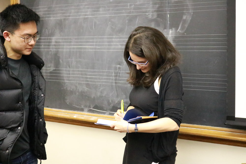 Sarah hurwitz signs a student's copy of her book after a speaker event
