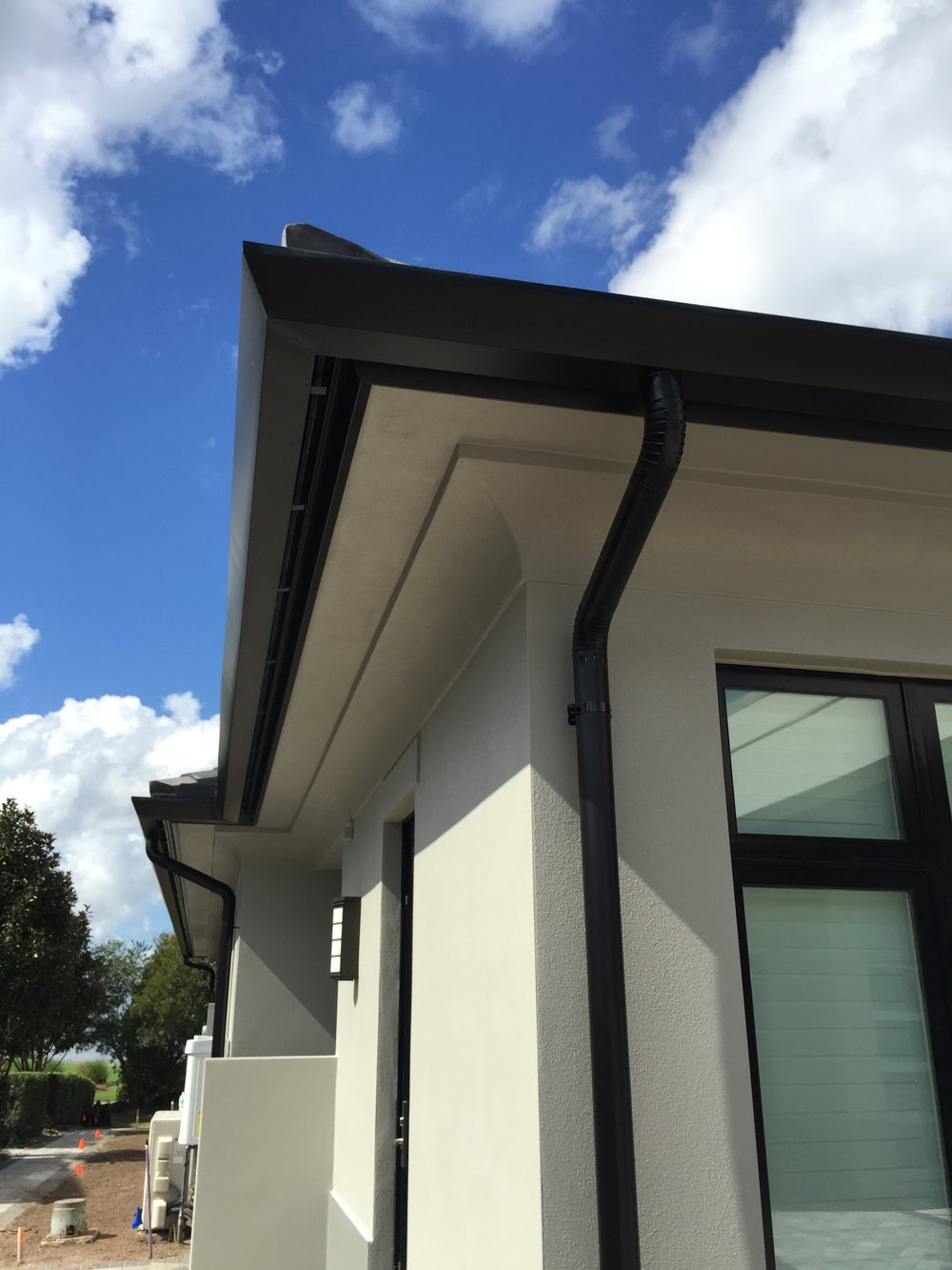 """7"""" CONTEMPORARY ALUMINUM GUTTER WITH 4"""" ROUND DOWNSPOUT ATTACHED WITH PIPE CLAMPS IN BRONZE"""