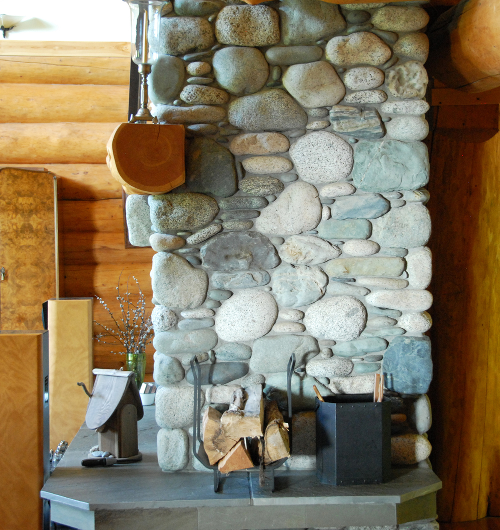 Side view of river rock fireplace, fir log mantel and bluestone hearth