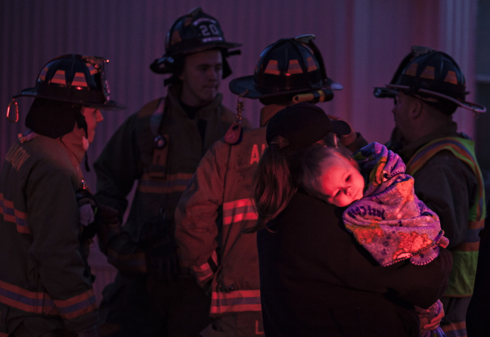 "An Emergency Medical Service worker holds Alessa Riney, 1, of Bowling Green, after she and her mother Shaina Riney had a furnace catch fire in the home on Friday, Jan. 29, 2016, at Greenwood Estates Mobile Home Park.  ""If it weren't for the smoke detector I wouldn't have known anything was going on,"" said Shaina Riney."