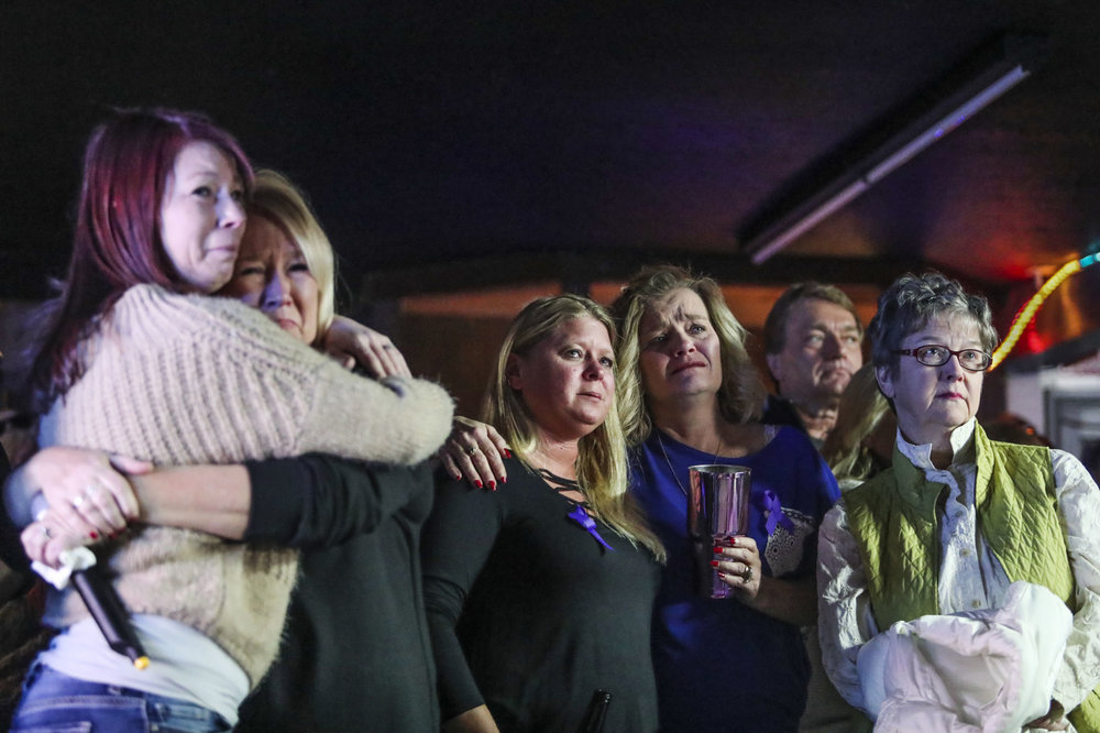 Friends and family of domestic violence homicide victim Betty Lasley watch a memorial video Sunday during a benefit held to raise money for funeral expenses at Betty's Bar.