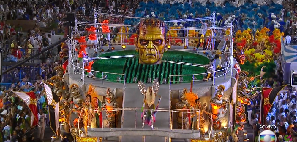 """A float shaped like a football stadium, the ultimate symbol of Brazil, is crowned by drag queens dancing in front of flags saying, among others, """"femicide, discrimination, racism, genocide, homophobia, hate."""""""