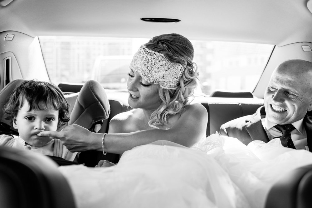 fotografía de boda novia en coche con padrino y niño emoción y felicidad blanco y negro