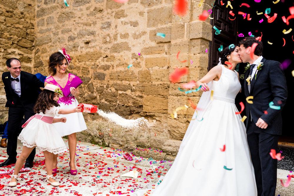 momento unico del arroz fuera de la iglesia tirado por la niña de arras con felicidad durante el beso de los novios