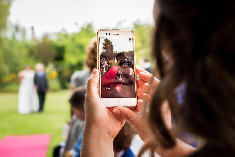 la entrada de la novia vista a través del móvil de una invitada
