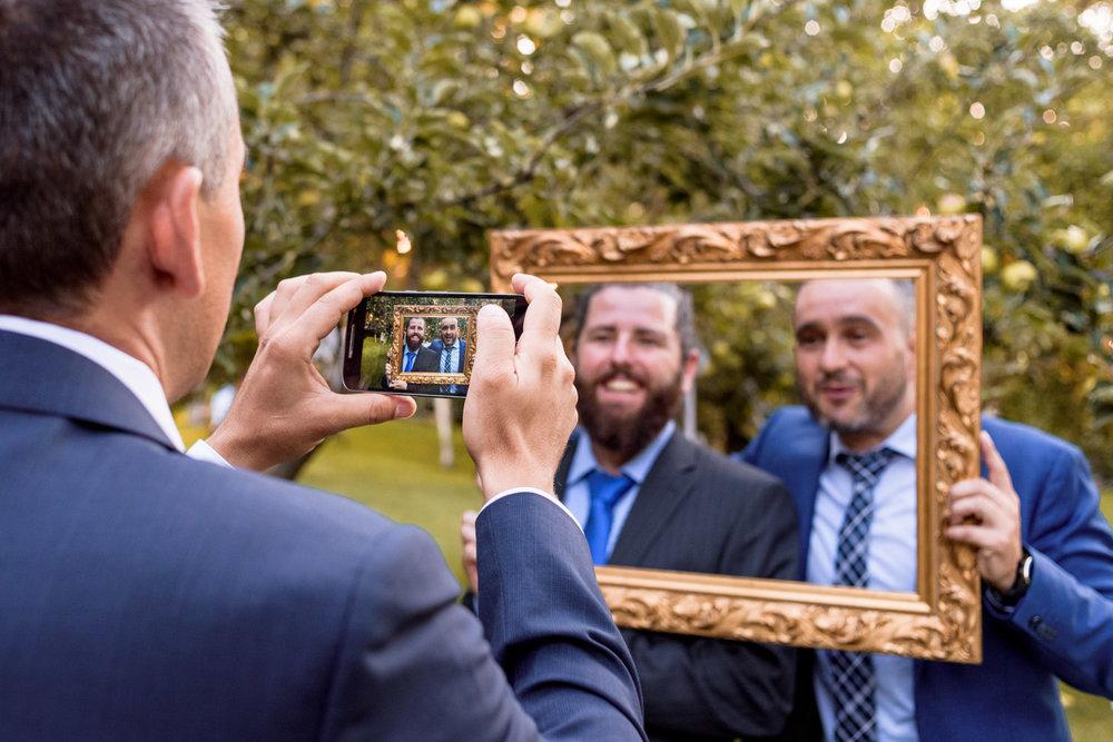 Alcuni invitati al matrimonio scattano foto con il proprio cellulare