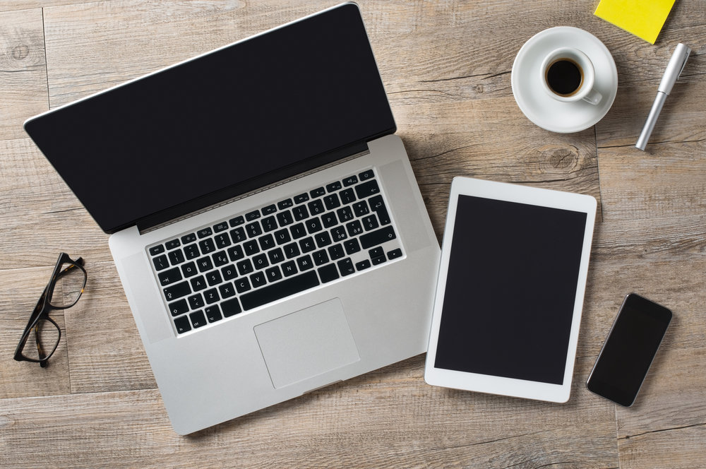 Laptop, iPad, iPhone and cup of coffee on a desk. Photo by Ridofranz/iStock