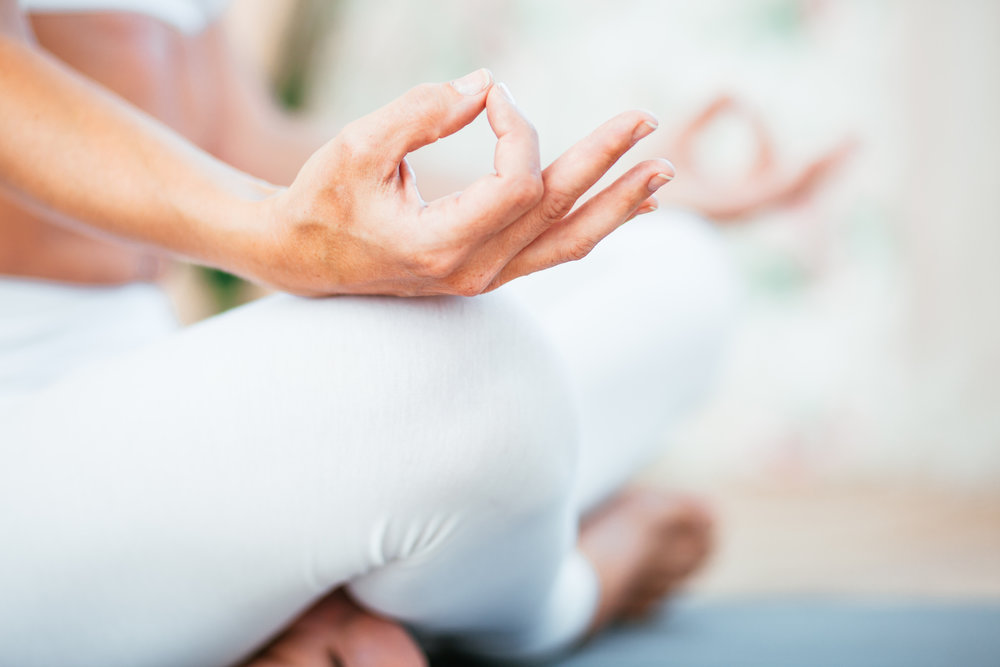 Woman doing yoga, sitting cross legged with hands on legs wearing white trousers or pants. Photo by Arand/iStock / Getty Images