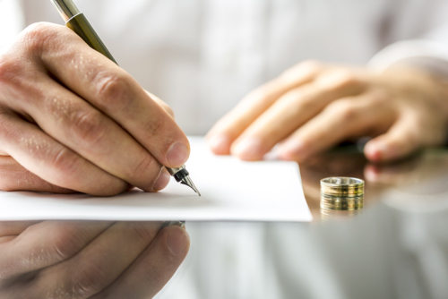Man signing divorce papers with gold wedding ring on desk table beside him
