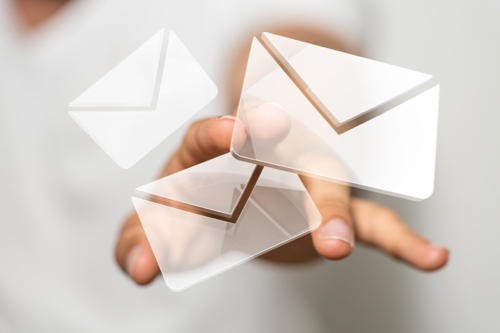 Transparent digital image of envelopes floating and being pointed at with fingers