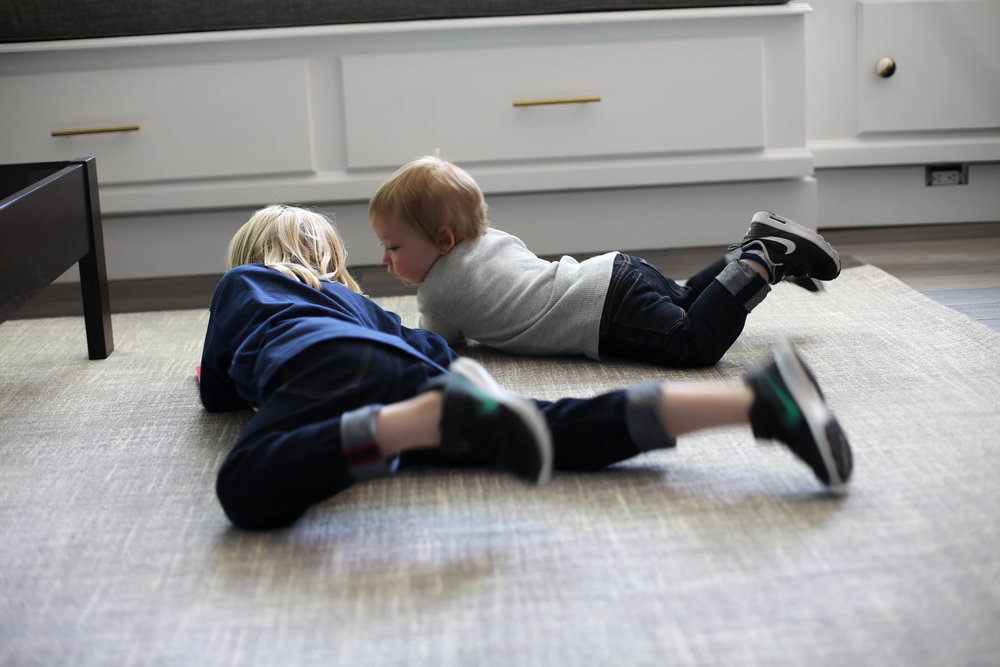 dash and albert rug, boys playing on the floor, gray rug