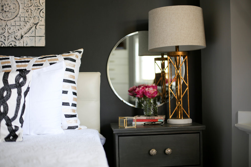 circle mirror, night stand, anthropologie hardware, master bedroom, black accent wall, gold chandelier, master bedroom retreat, rustic bedroom, chic bedroom, gold lighting, french gold, black and white bedroom, peonies