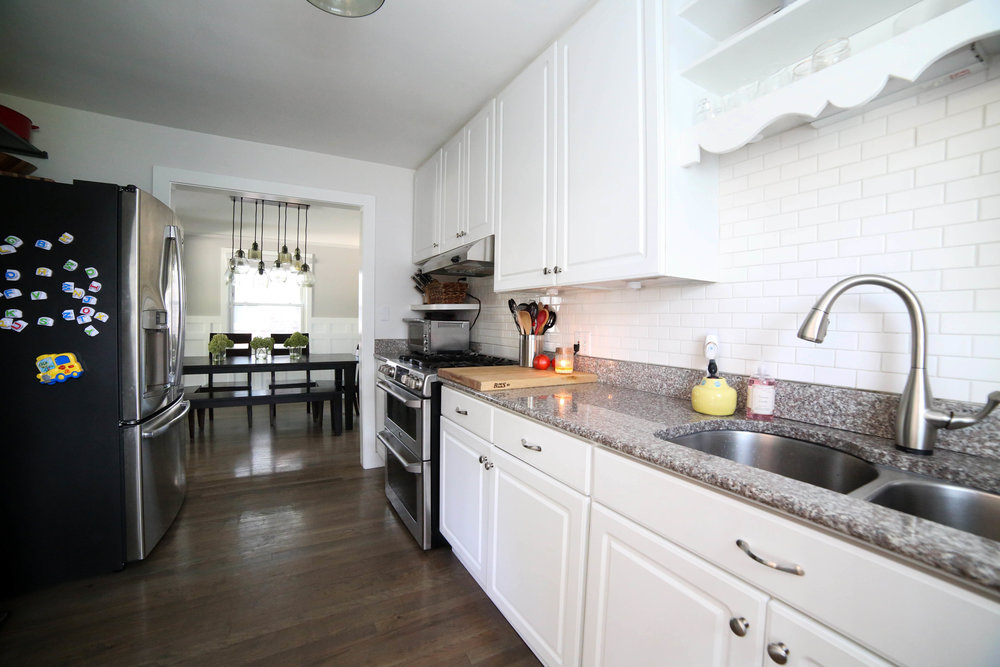 all white kitchen, subway tile backsplash, white cabinets, granite counter tops, pottery barn lighting, ge fridge , ge range