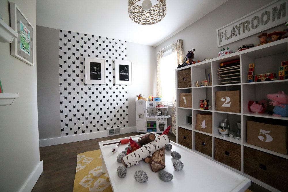 how to add character to any kids room, playroom, kids playroom, storage bins, play kitchen, pretend play, wall mural, black and white playroom, numbered storage bins, how to add character to any kids room, toy storage, number bins, toys, how to store toys, playroom, kids room, storage, toy storage, how to add character to any kids room, bookshelf, rain gutter bookshelf, rain gutter bookshelves, art work, pete the cat art work, kids picture books