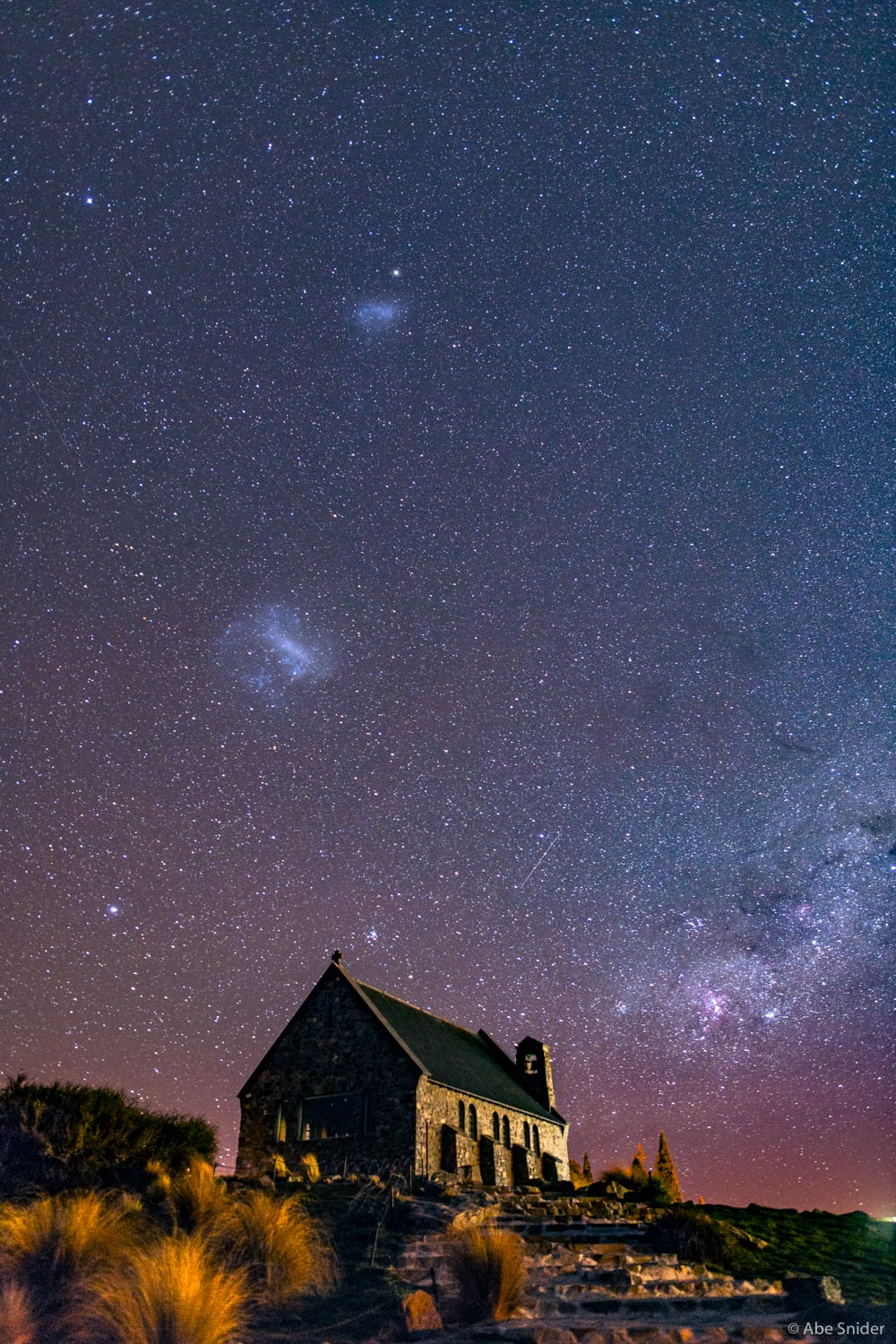 A wider shot of the LMC & SMC above the Church of the Good Shepard in Lake Tekapo, New Zealand. The Carina Nebula is off to the lower right.