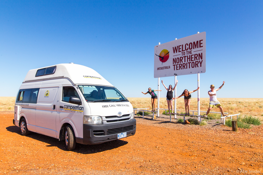 """Roo"" our van, and the four of us on the way to Uluru! I won't admit how many times we had to try to get this photo, we all kept falling off the railing!"
