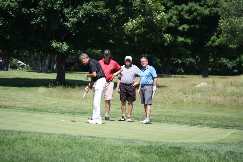 Carl Bailey sets up to putt his ball while his teammates Geoff Dent, Marty Rader, and Arnie Finaldi look on.