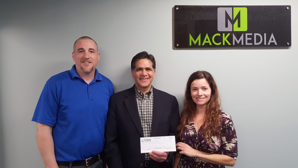 Newtown Scholarship Association President, Glenn Nanavaty (center), accepts a donation in the amount $22,239.52 from Scott and Carla Johnson, owners of Mack Media Group and founders of the Newtown Strong Fund.